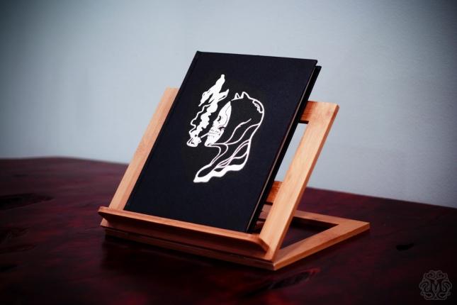 """「モンド ブック IV -スモーキング キルズ-」Mondo Book Vol. IV – """"Smoking Kills"""" Cover design by We Buy Your Kids. 9""""x12"""" leather bound, hardcover scratch and dent poster book.  Embossed design with silver inlay.  Assembled by hand. Hand numbered.  Edition of 100.  US$200"""