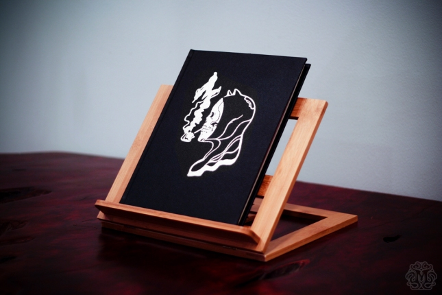 "「モンド ブック IV -スモーキング キルズ-」Mondo Book Vol. IV – ""Smoking Kills"" Cover design by We Buy Your Kids. 9""x12"" leather bound, hardcover scratch and dent poster book.  Embossed design with silver inlay.  Assembled by hand. Hand numbered.  Edition of 100.  US$200"